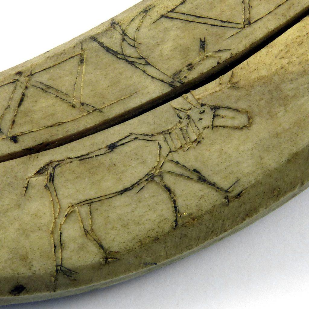 An incised reindeer design on a Sammi knife sheath made of reindeer antler
